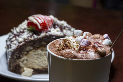 Lavish hot chocolate with marshmallows and a slice of roulade